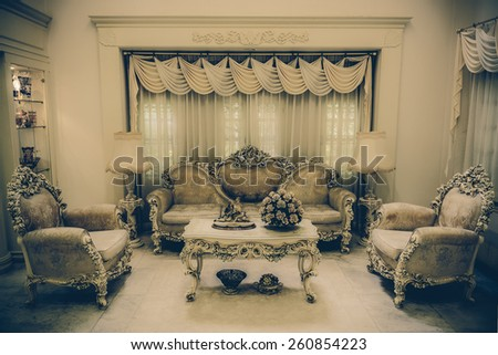 A grand living room interior architecture with various furniture in a residential house home with a luxurious and haunting retro color style.  - stock photo
