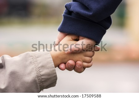 A grand-mother holding her grand-son's hand in hand - stock photo