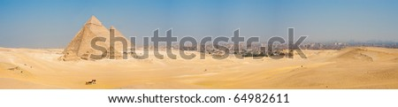 A grand panorama of all of the pyramids at Giza and the city of Cairo, Egypt nearby - stock photo