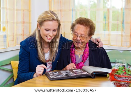 a grandchild visiting his grandmother. view the photo album. - stock photo