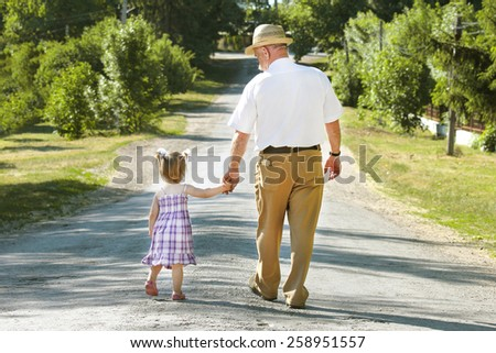 a grandfather and granddaughter are on the road - stock photo