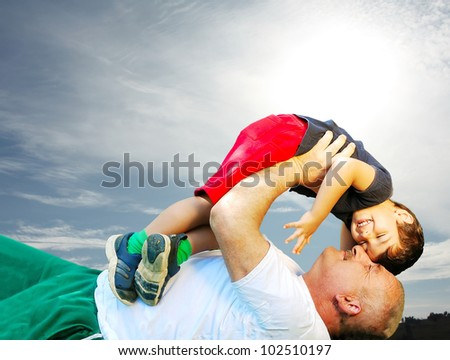 A grandfather and his kid laying and smiling on grass - stock photo