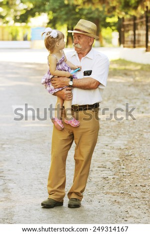 a grandfather with his granddaughter are on the road - stock photo