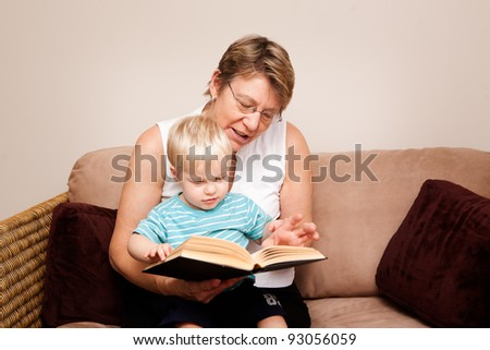 A grandmother, Nanny or au pair reads to a little boy indoors - stock photo