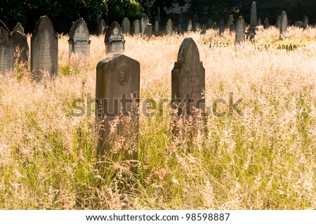 a graveyard with gravestones and tombs - stock photo