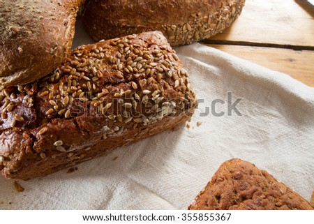 A great variety of loaves of bread against a wooden background: multi-grain, spelt, sourdough, rye and gluten-free for celiacs or gluten-intolerant people. - stock photo