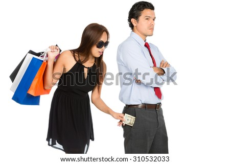 A greedy woman shopaholic with department store shopping bags secretly removing money unnoticed from her pushover husband pants pocket while standing and looking away. H - stock photo