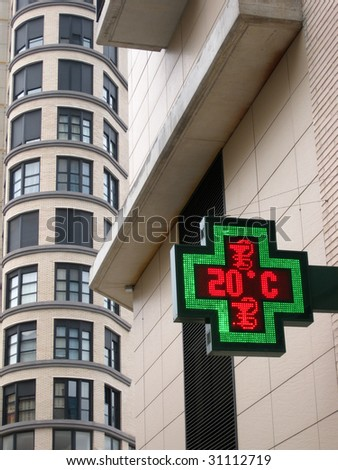 A green and red neon pharmacy sign with a building in the background - stock photo