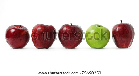 A green apple being stood out among red apples isolated on white background. - stock photo