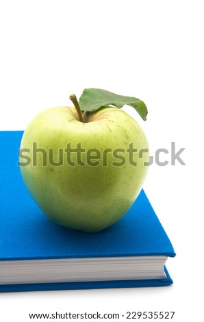 A green apple on a book - stock photo