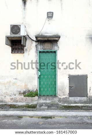 A green color metal old backdoor on a dilapidated building wall, in a back alley.   - stock photo