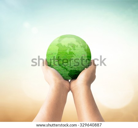 A green earth globe of grass in human hands over blurred beautiful nature background. World Environment Day. Ecological city concept. - stock photo