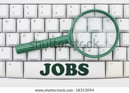 A green magnify glass on a computer keyboard, Job Searching - stock photo
