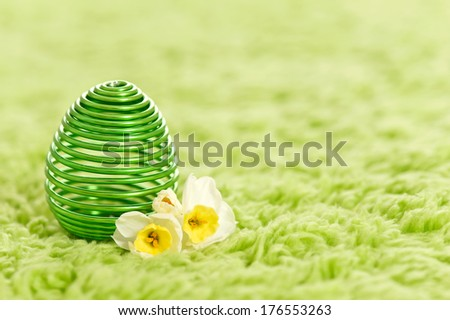 A green metal spiral egg sits on a green shag carpet with two flowers beside it. - stock photo