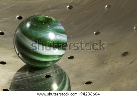 A green onionskin lutz marble on a metal strainer. - stock photo