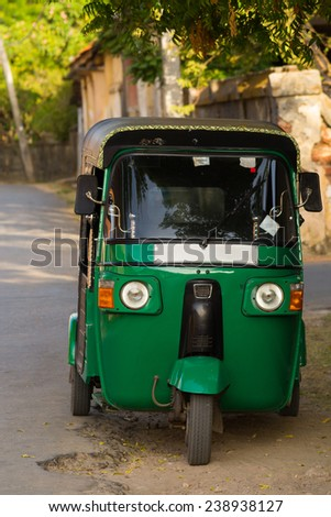 A green rickshaw (taxi) waiting for customers in Jaffna, Sri Lanka. - stock photo