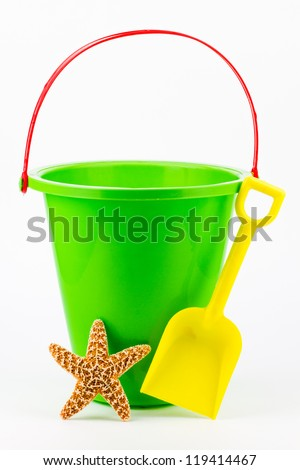 A green sand bucket with a yellow shovel and a starfish. - stock photo