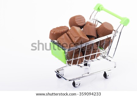 A green shopping cart trolley with a few organic chocolate on a white background - stock photo