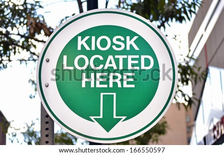 A green sign reading Kiosk Located Here - stock photo