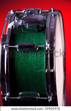 A green snare drum isolated against a redbackground in the vertical format. - stock photo