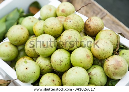 A green star apple (Chrysophyllum cainito or Swarnapathry) fruits for sale on the street market in Vietnam - stock photo