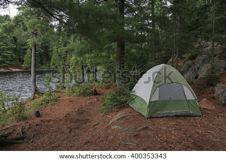 A green tent setup right beside a lake.  Shot in Algonquin Provincial Park, Ontario, Canada.  - stock photo