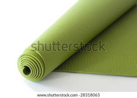 A green yoga/pilates/exercise mat rolled up on white. - stock photo