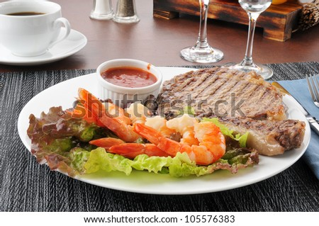 A grilled rib steak with tiger shrimp prawns - stock photo