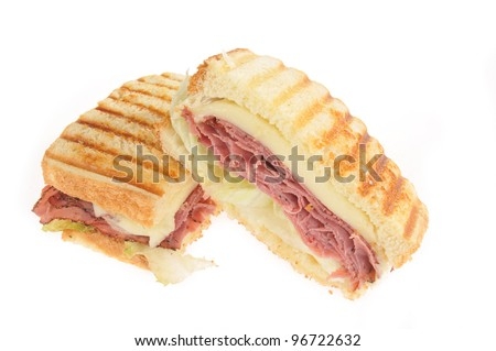 A grilled roast beef panini with swiss cheese on a white background - stock photo