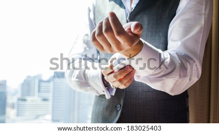 A groom putting on cuff-links as he gets dressed in formal wear  - stock photo