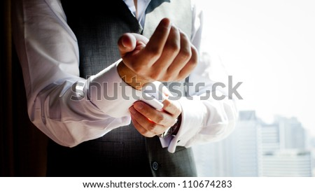 A groom putting on cuff-links as he gets dressed in formal wear .Groom's suit - stock photo