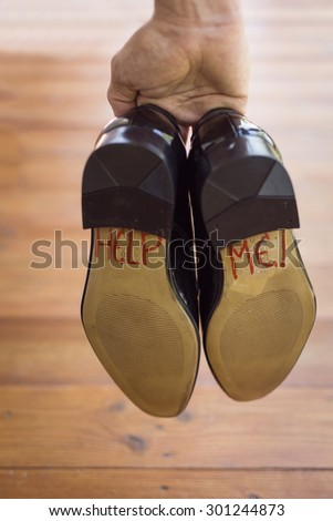 A groom with the words help on the bottom of his shoes.