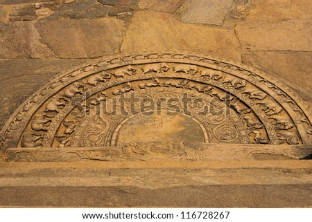 A ground carving at the entrance to the Vatadage is a moonstone relief depicting the cycle of sansara in the ruins of ancient capitol of Polonnaruwa, Sri Lanka - stock photo
