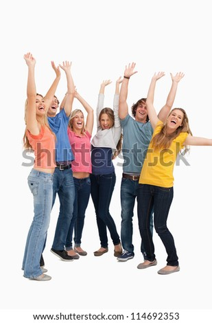 A group looking to the side as they jump in the air while cheering - stock photo