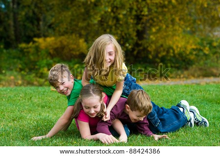 A group of active kids playing in a dog pile on grass. - stock photo