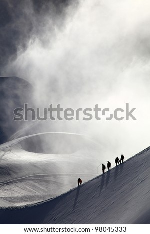 A group of alpinists on their way to the mont blanc at dawn. - stock photo