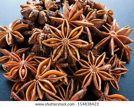 A group of anise stars on the black background. Shallow dof. - stock photo