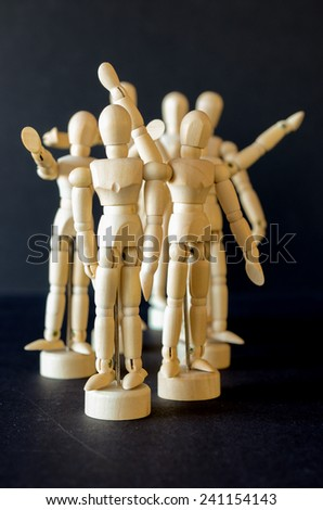 A group of artist manikins with arms raised to signify anger, cheering, waving or joy - stock photo