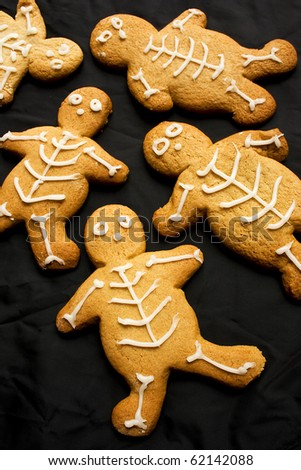 A group of baked gingerbread men on a black cloth background - stock photo