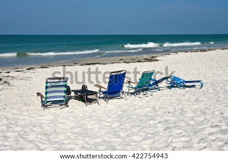 A Group of Beach Chairs on a White Sandy Beach  - stock photo
