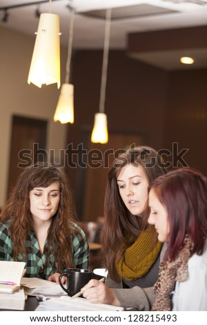A group of beautiful young women talk around a table with bibles and notebooks. - stock photo