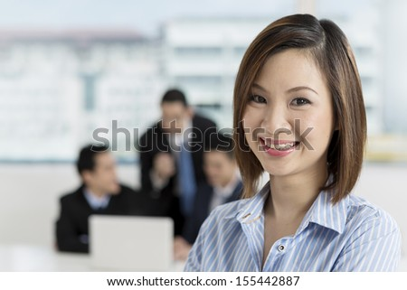 A group of business people lead by a happy Chinese Businesswoman. - stock photo