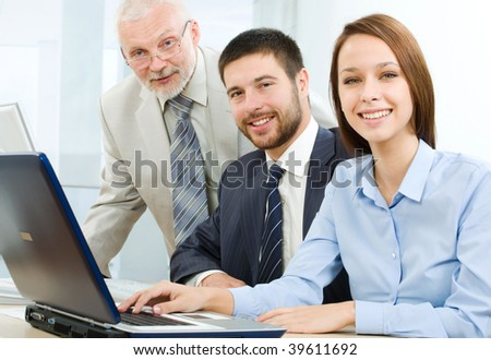 A group of business people sitting at table, looking at camera - stock photo
