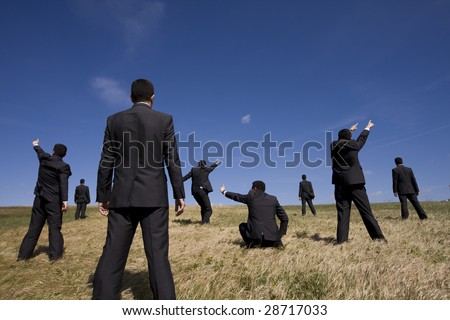 a group of businessman at the field searching for something - stock photo