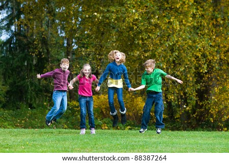A group of children holding hands and jumping in the air. - stock photo