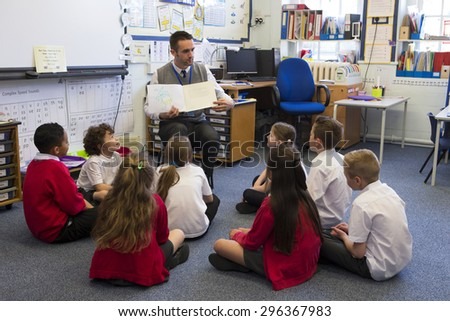 A group of children sit on the floor cross legged, listening to the teacher read a story. - stock photo