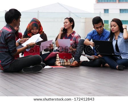 A group of college students studying outside campus building - stock photo