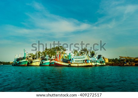 A group of colorful fishing boats at sunset, Mae Klong river, Thailand. - stock photo