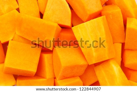 A group of cut and slice butternut squash chunks on  background. - stock photo