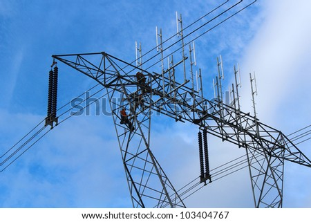 A group of dedicated hydro workers bravely work on an electrical power station tower. - stock photo